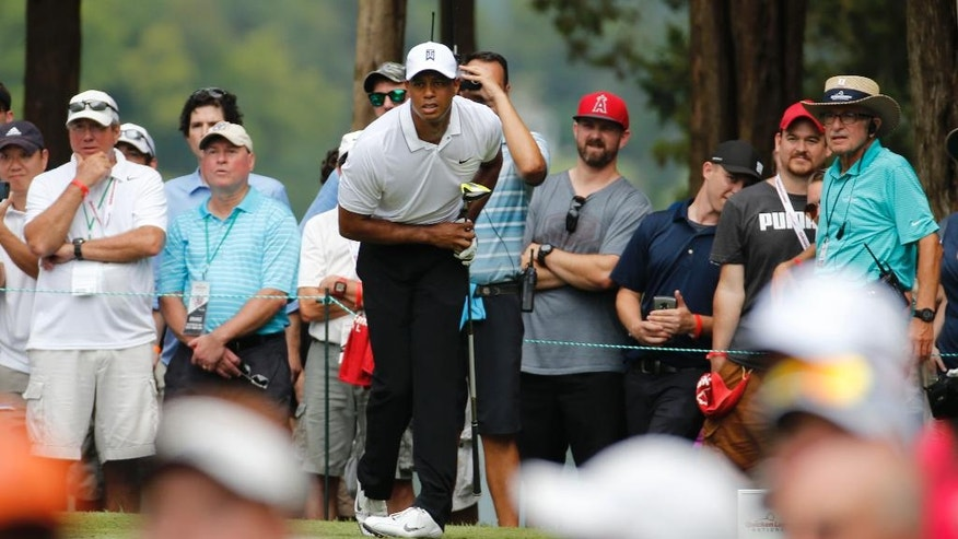 Tiger Woods watches his tee shot on the second hole during the first round of the Quicken Loans National golf tournament at the Robert Trent Jones Golf Club in Gainesville, Va., Thursday, July 30, 2015.  The ball ended up in a bunker. (AP Photo/Steve Helber)