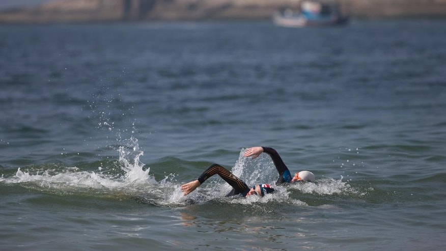 "Paratriathletes swim in the waters of Copacabana Beach during a training session, in Rio de Janeiro, Brazil, Friday, July 31, 2015. The Brazilian government's data on water pollution in Rio de Janeiro show water near where triathletes are preparing to compete this weekend is ""unfit"" for swimming. The most recent pollution reading at Copacabana was taken from a sample this past Monday. An Olympic qualifier and Paratriathlon event begins Saturday, and several athletes were already getting into the water Friday morning. (AP Photo/Silvia Izquierdo)"