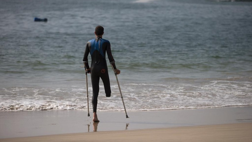 "Paratriathlete stands on the shore of the Copacabana Beach during a training session, in Rio de Janeiro, Brazil, Friday, July 31, 2015. The Brazilian government's data on water pollution in Rio de Janeiro show water near where triathletes are preparing to compete this weekend is ""unfit"" for swimming. The most recent pollution reading at Copacabana was taken from a sample this past Monday. An Olympic qualifier and Paratriathlon event begins Saturday, and several athletes were already getting into the water Friday morning. (AP Photo/Silvia Izquierdo)"