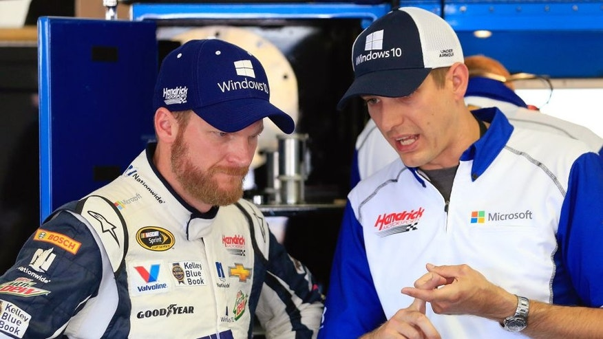 Dale Earnhardt Jr., driver of the #88 Microsoft Chevrolet, left, talks with crew chief Greg Ives in the garage area during practice for the NASCAR Sprint Cup Series Windows 10 400 at Pocono Raceway on July 31, 2015 in Long Pond, Pennsylvania. (Photo by Chris Trotman/Getty Images)