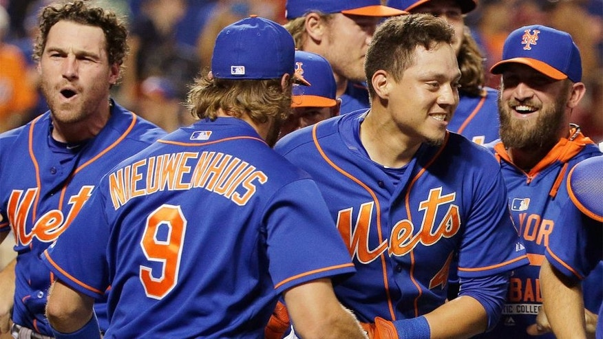 New York Mets' Wilmer Flores, center right, is mobbed by teammates after hitting a walkoff solo home run during the twelfth inning of a baseball game to defeat the Washington Nationals 2-1, Friday, July 31, 2015, in New York. (AP Photo/Julie Jacobson)