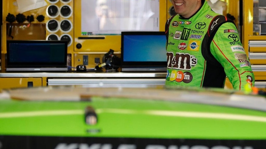Kyle Busch smiles while waiting for the start of a practice session for Sunday's NASCAR Pocono 400 auto race, Friday, July 31, 2015, in Long Pond, Pa. (AP Photo/Matt Slocum)