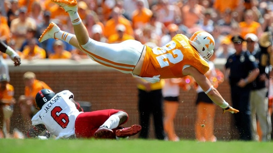 Sep 6, 2014; Knoxville, TN, USA; Tennessee Volunteers tight end Ethan Wolf (82) jumps over Arkansas State Red Wolves running back Frankie Jackson (6) during the second half at Neyland Stadium. Tennessee won 34 to 19. Mandatory Credit: Randy Sartin-USA TODAY Sports