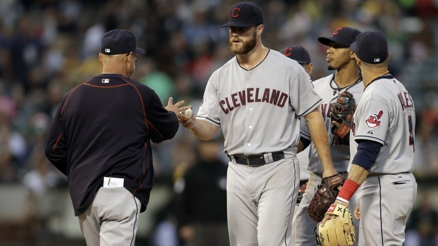 Cleveland Indians' Cody Anderson, center, hands the ball to manager Terry Francona after being removed in the seventh inning of a baseball game against the Oakland Athletics, Saturday, Aug. 1, 2015, in Oakland, Calif.
