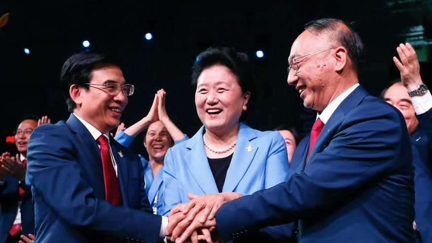 China's Vice Premier Liu Yandong, center, celebrates with Beijing Mayor and Beijing 2022 Olympic Winter Games Bid President Wang Anshun, left, and Liu Peng, right, Minister of the General Administration of Sport of China, after Beijing was awarded the 2022 Winter Olympic Games, defeating Almaty in the final round of voting, at IOC meeting in Kuala Lumpur, Malaysia, Friday, July 31, 2015. (AP Photo/Vincent Thian, Pool)