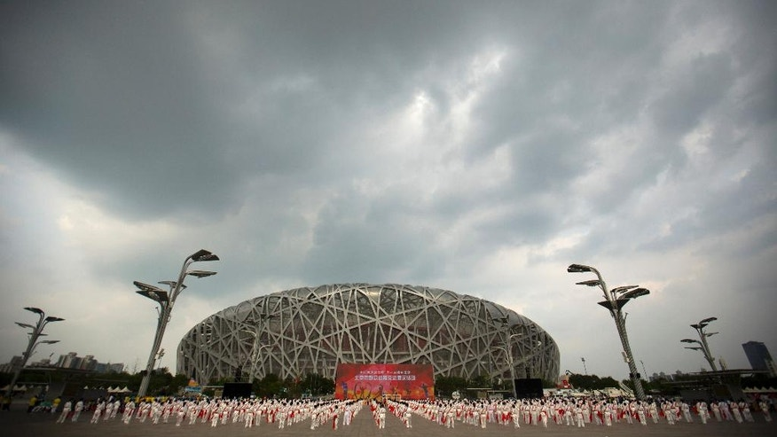 Participants dance under threatening skies at a gathering to watch the announcement of the 2022 Winter Olympics host city outside the Beijing Olympic Stadium, also known as the Birds Nest, in Beijing, Friday, July 31, 2015. Beijing was selected Friday to host the 2022 Winter Olympics, becoming the first city awarded both the winter and summer games. (AP Photo/Mark Schiefelbein)
