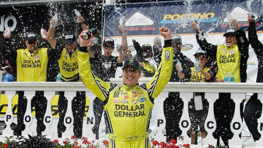 Kyle Busch celebrates in victory lane after winning the NASCAR truck series Pocono Mountains 150 auto race, Saturday, Aug. 1, 2015, in Long Pond, Pa. (AP Photo/Matt Slocum)
