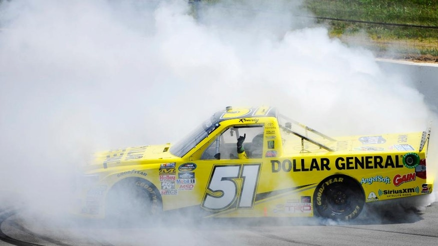 Kyle Busch smokes his tires after winning the NASCAR truck series Pocono Mountains 150 auto race, Saturday, Aug. 1, 2015, in Long Pond, Pa. (AP Photo/Derik Hamilton)