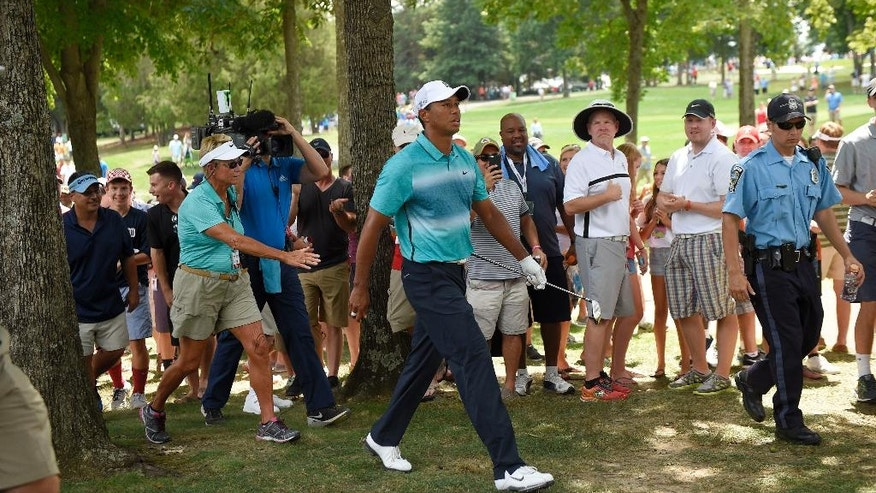 Tiger Woods walks past the gallery after he hit out of the rough on the second hole during the third round of the Quicken Loans National golf tournament at the Robert Trent Jones Golf Club in Gainesville, Va., Saturday, Aug. 1, 2015. (AP Photo/Nick Wass)