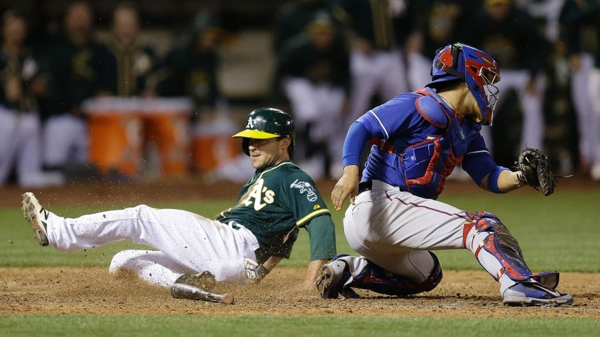 Oakland Athletics' Sam Fuld, left, slides to score behind Texas Rangers catcher Robinson Chirinos in the ninth inning of a baseball game Wednesday, June 10, 2015, in Oakland, Calif. The A's scored the winning run on the play, on a single by Josh Reddick. (AP Photo/Ben Margot)