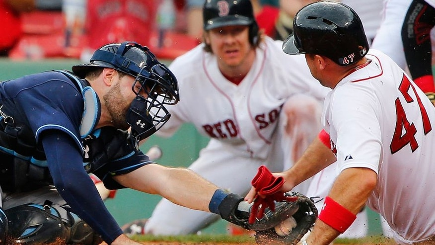 Boston Red Sox's Travis Shaw slides safely into home around the tag of Tampa Bay Rays catcher Curt Casali during the sixth inning of a baseball game at Fenway Park in Boston Saturday, Aug. 1, 2015. (AP Photo/Winslow Townson)