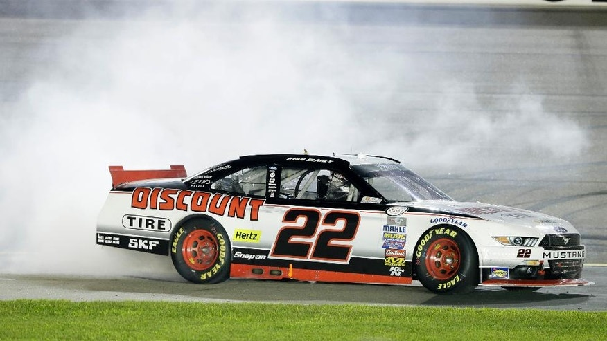 Ryan Blaney does a burnout after winning the NASCAR Xfinity Series auto race, Saturday, Aug. 1, 2015, at Iowa Speedway in Newton, Iowa. (AP Photo/Charlie Neibergall)