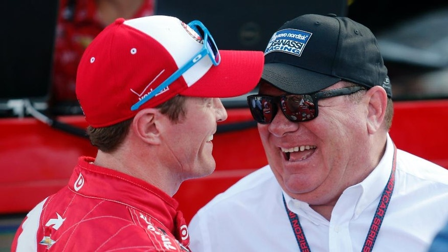 Scott Dixon, of New Zealand, left, talks with car owner Chip Ganassi after winning the pole position for the IndyCar Honda Indy 200 auto racing Saturday, Aug. 1, 2015, at Mid-Ohio Sports Car Course in Lexington, Ohio. (AP Photo/Tom E. Puskar)