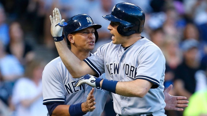 New York Yankees designated hitter Alex Rodriguez, left, celebrates with teammate Mark Teixeira after Teixeira's grand slam during the second inning of a baseball game against the Chicago White Sox in Chicago, Friday, July 31, 2015. (AP Photo/Jeff Haynes)
