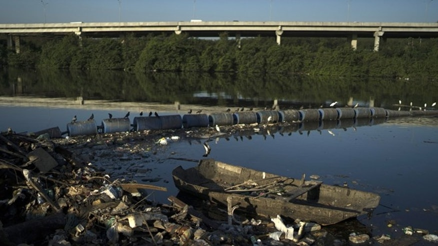 A discarded boat and trash abut floating waste barriers in a canal at the Mare slum complex, in Rio de Janeiro, Brazil, Friday, July 31, 2015. Rio's historic sewage problem spiraled over the past decade as the population exploded with many of the metropolitan area's 12 million residents settling in the vast slums that ring the bay. Waste flows into over 50 streams that empty into the once-crystalline Guanabara Bay. (AP Photo/Leo Correa)