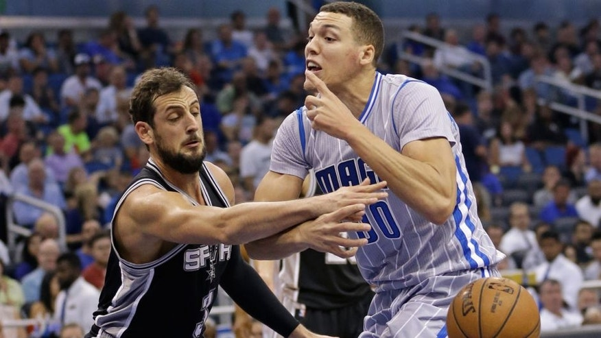 San Antonio Spurs' Marco Belinelli, left, knocks the ball out of the hands of Orlando Magic's Aaron Gordon, forcing a turnover, during the first half of an NBA basketball game, Wednesday, April 1, 2015, in Orlando, Fla. (AP Photo/John Raoux)