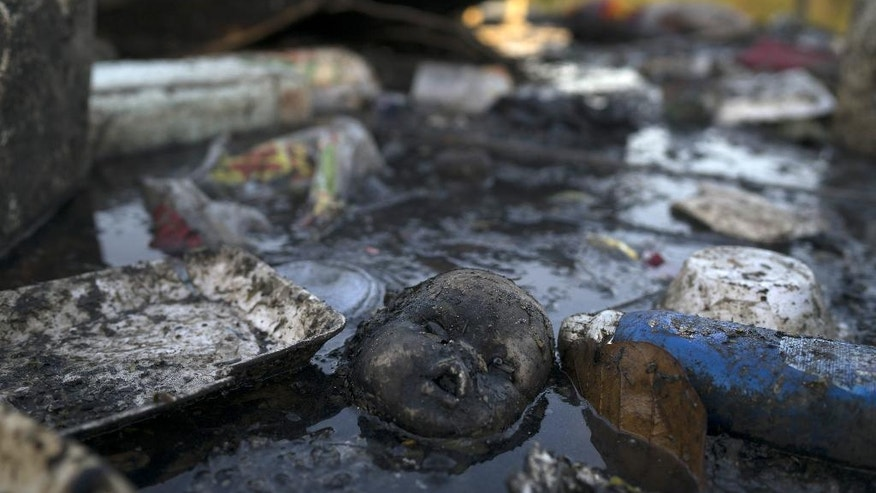 A doll's head floats in the polluted waters of a canal at the Mare slum complex in Rio de Janeiro, Brazil, Friday, July 31, 2015. In Rio, much of the waste runs through open-air ditches to fetid streams and rivers that feed the Olympic water sites and blight the city's picture postcard beaches. (AP Photo/Leo Correa)