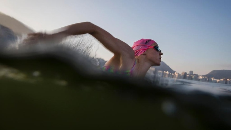 "A triathlete trains in the waters off Copacabana Beach, despite published warnings that water in the area was ""unfit"" for swimming, in Rio de Janeiro, Brazil, Friday, July 31, 2015. Athletes said that the conditions of the water appeared better than they were expecting. But water experts and the government's own pollution monitoring officials all note that sewage pollution typically isn't something that can be seen by the naked eye. (AP Photo/Felipe Dana)"