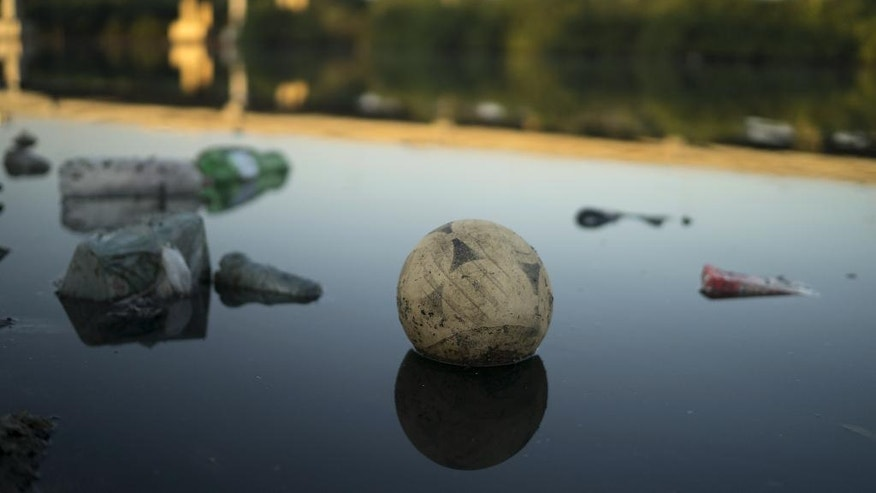 A discarded ball floats on the water in a canal at the Mare slum complex  in Rio de Janeiro, Brazil, Friday, July 31, 2015. In Rio, much of the waste runs through open-air ditches to fetid streams and rivers that feed the Olympic water sites and blight the city's picture postcard beaches. (AP Photo/Leo Correa)