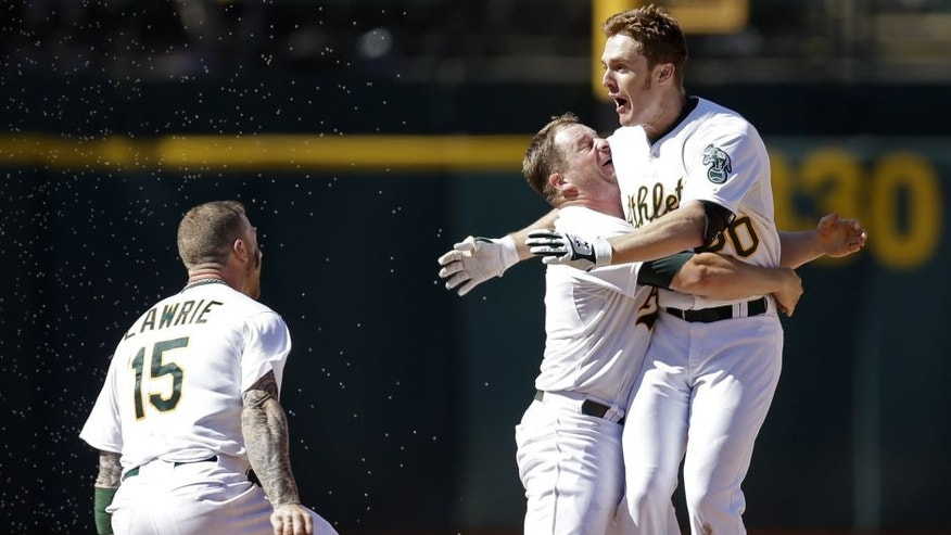 Oakland Athletics' Stephen Vogt, center, lifts Mark Canha after Canha hit the game winning hit in the tenth inning of a baseball game against the Cleveland Indians, Sunday, Aug. 2, 2015, in Oakland, Calif. At left is A's Brett Lawrie (15). The A's won, 2-1.