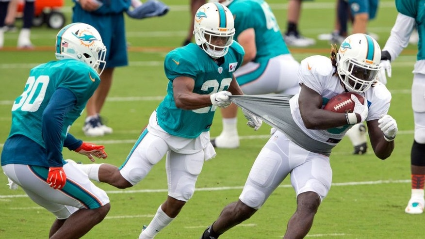 Miami Dolphins cornerback Bobby McCain (28) attempts to slow down Miami Dolphins running back Jay Ajayi (33) during NFL training camp, Saturday, Aug. 1, 2015 at Nova Southeastern University in Davie, Fla. (Al Diaz/The Miami Herald via AP) MAGS OUT; MANDATORY CREDIT