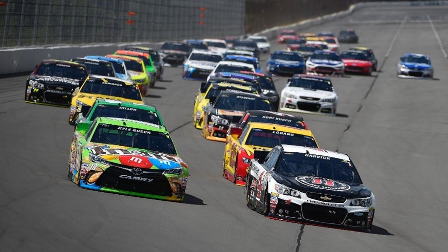 Kyle Busch (18) and Kevin Harvick (4) lead the field into Turn 1 during the NASCAR Pocono 400 auto race, Sunday, Aug. 2, 2015, in Long Pond, Pa. (AP Photo/Derik Hamilton)