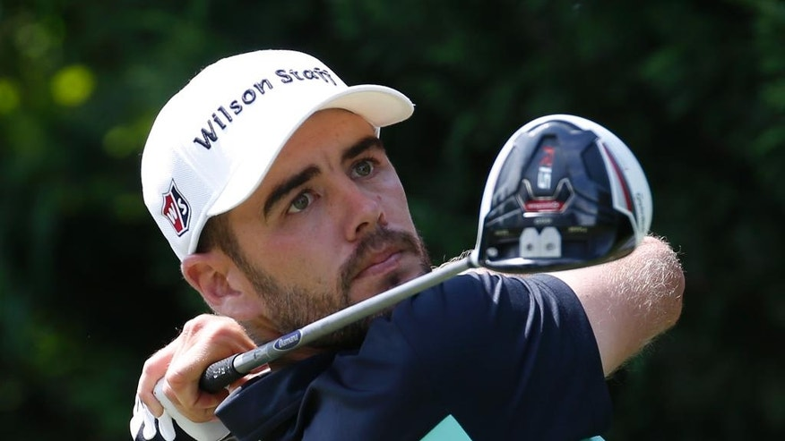 Troy Merritt watches his tee shot on the third hole during the final round of the Quicken Loans National golf tournament at the Robert Trent Jones Golf Club in Gainesville, Va., Sunday, Aug. 2, 2015. (AP Photo/Steve Helber)