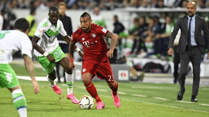 Bayern Munich's Chilean midfielder Arturo Vidal (C) runs with the ball during the German Supercup football match VfL Wolfsburg vs Bayern Munich in Wolfsburg, central Germany, on August 1, 2015. Wolfsburg wins 5-4. AFP PHOTO / TOBIAS SCHWARZ DFL RULES TO LIMIT THE ONLINE USAGE DURING MATCH TIME TO 15 PICTURES PER MATCH. IMAGE SEQUENCES TO SIMULATE VIDEO IS NOT ALLOWED AT ANY TIME. FOR FURTHER QUERIES PLEASE CONTACT DFL DIRECTLY AT + 49 69 650050. (Photo credit should read TOBIAS SCHWARZ/AFP/Getty Images)