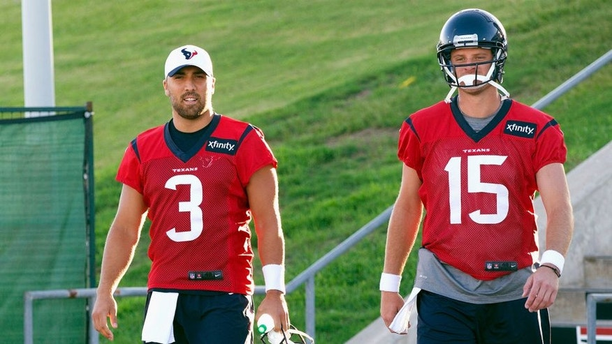 Houston Texans quarterbacks Tom Savage (3) and Ryan Mallett (15) arrive for an NFL football training camp at the Methodist Training Center, Saturday, Aug. 1, 2015, in Houston. (AP Photo/Bob Levey)