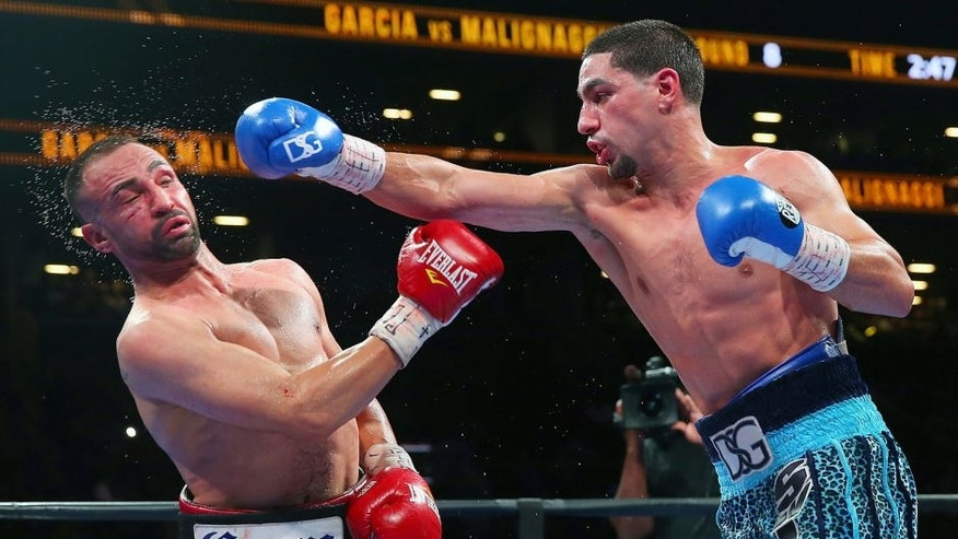 NEW YORK, NY - AUGUST 01: Danny Garcia (R) lands a punch against Paulie Malignaggi during their welterweight bout at Barclays Center on August 1, 2015 in Brooklyn borough of New York City. (Photo by Mike Stobe/Getty Images)