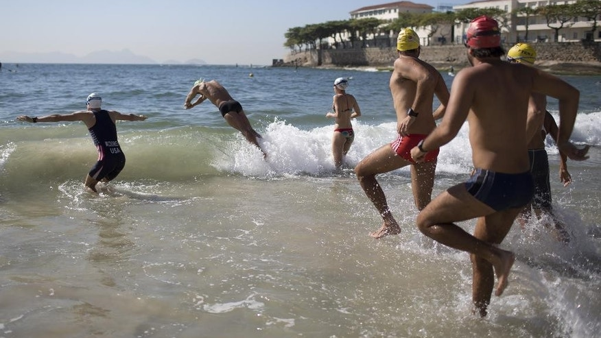 "Triathlon athlete Kevin Mcdowell, left, of the U.S., and local swimmers enter the water for a swimming clinic along Copacabana beach in Rio de Janeiro, Brazil, Monday, Aug. 3, 2015. Triathletes swam in waters off Copacabana Beach despite published warnings that water in the area was ""unfit"" for swimming. On Thursday, The Associated Press released the results of a five-month investigation that showed that Olympic venues are rife with disease-causing viruses and bacteria. (AP Photo/Leo Correa)"