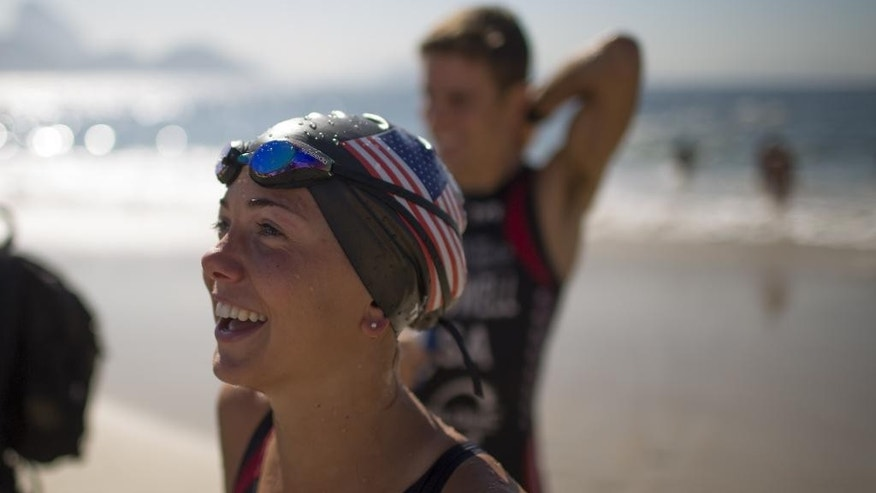 "Triathlon athlete Erin Jones, of the U.S., smiles as fellow swimmer Kevin Mcdowell stand behind after they gave a swimming clinic to local swimmers along Copacabana beach in Rio de Janeiro, Brazil, Monday, Aug. 3, 2015. Triathletes swam in waters off Copacabana Beach despite published warnings that water in the area was ""unfit"" for swimming. On Thursday, The Associated Press released the results of a five-month investigation that showed that Olympic venues are rife with disease-causing viruses and bacteria. (AP Photo/Leo Correa)"