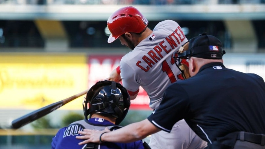 St. Louis Cardinals' Matt Carpenter, flies out as Colorado Rockies catcher Nick Hundley, center, and home plate umpire Mike Everitt look on in the first inning of a baseball game Monday, June 8, 2015, in Denver. (AP Photo/David Zalubowski)