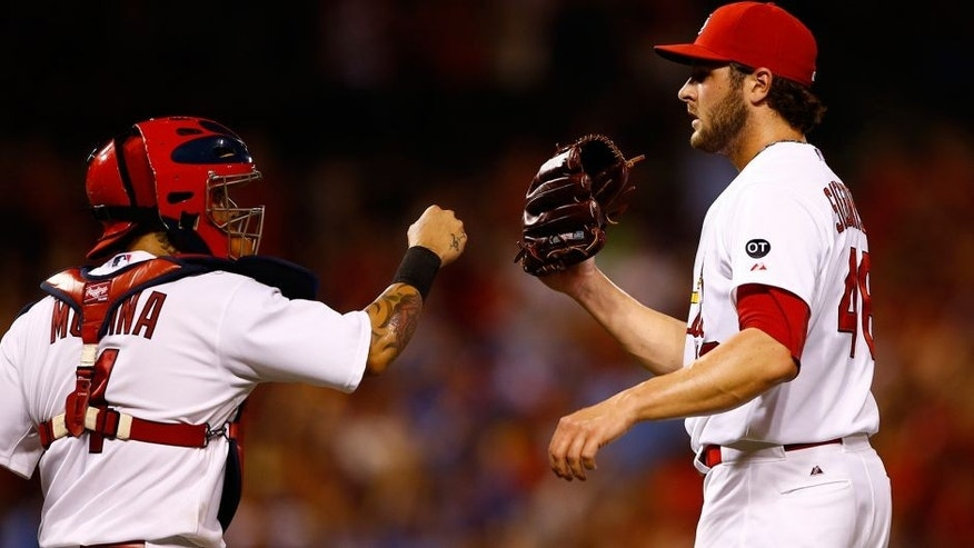 St. Louis Cardinals catcher Yadier Molina, left, celebrates with relief pitcher Kevin Siegrist after defeating the Kansas City Royals in a baseball game Friday, June 12, 2015, in St. Louis. (AP Photo/Billy Hurst)