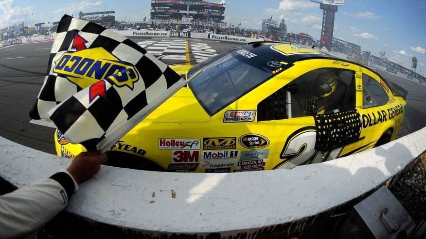 LONG POND, PA - AUGUST 02: Matt Kenseth, driver of the #20 Dollar General Toyota, celebrates with the checkered flag after winning the NASCAR Sprint Cup Series Windows 10 400 at Pocono Raceway on August 2, 2015 in Long Pond, Pennsylvania. (Photo by Jared C. Tilton/Getty Images)