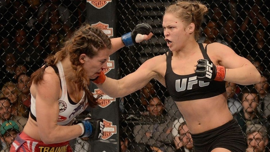 LAS VEGAS, NV - DECEMBER 28: (R-L) Ronda Rousey punches Miesha Tate in their UFC women's bantamweight championship bout during the UFC 168 event at the MGM Grand Garden Arena on December 28, 2013 in Las Vegas, Nevada. (Photo by Donald Miralle/Zuffa LLC/Zuffa LLC via Getty Images)
