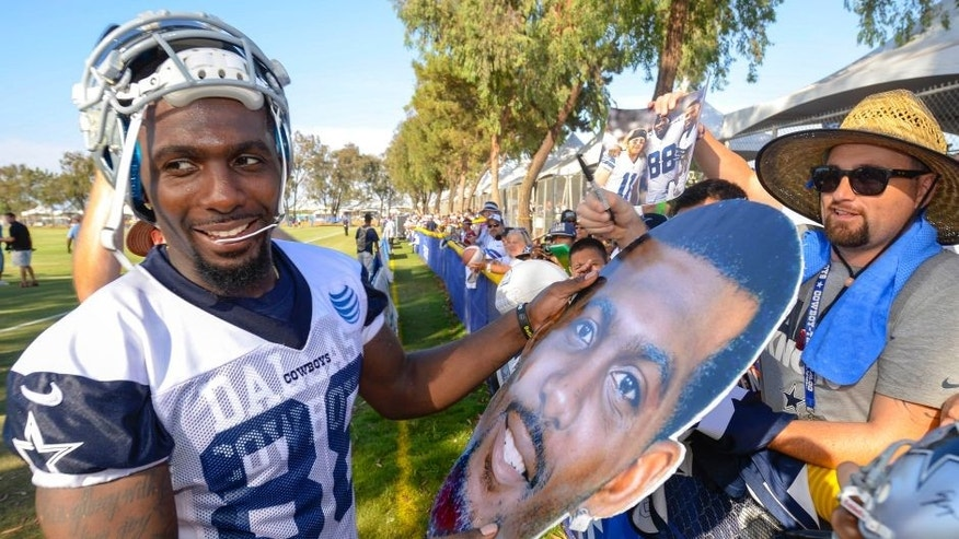Dallas Cowboys wide receiver Dez Bryant is handed a large cutout photo of his head to sign after afternoon practice during NFL football training camp, Friday, July 31, 2015, in Oxnard, Calif. (AP Photo/Gus Ruelas)