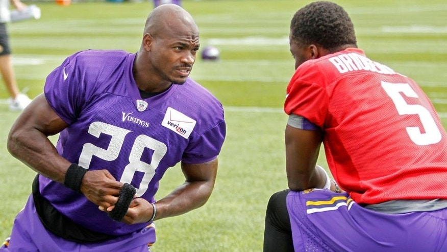 Jul 27, 2015; Mankato, MN, USA; Minnesota Vikings running back Adrian Peterson (28) talks with quarterback Teddy Bridgewater (5) before drills at training camp at Minnesota State University. Mandatory Credit: Bruce Kluckhohn-USA TODAY Sports