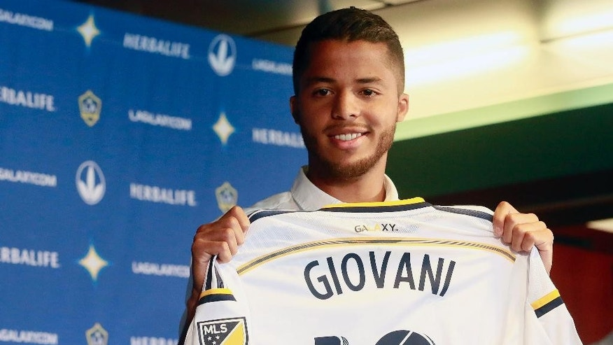Los Angeles Galaxy forward Giovani dos Santos shows his new jersey at an introductory news conference in Carson, Calif., on Tuesday, Aug. 4, 2015. After four years of courting dos Santos, the Galaxy signed the highest-profile Mexican star in their history to a designated player contract, paying a reported $7 million transfer fee. He is expected to make his debut on Sunday against the Seattle Sounders FC. (AP Photo/Nick Ut)