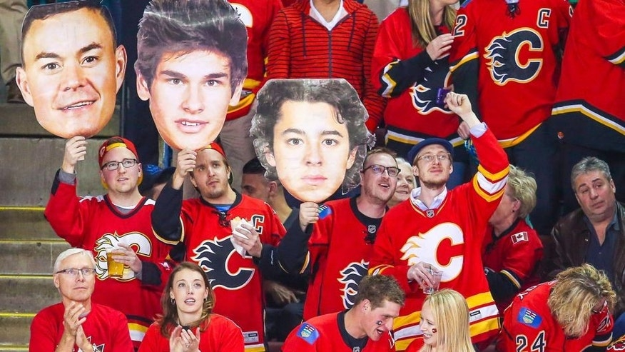 Apr 9, 2015; Calgary, Alberta, CAN; Calgary Flames fans hold cardboard cutouts of Jiri Hudler (not pictured), Sean Monahan (not pictured) and Johnny Gaudreau (not pictured) during the first period against the Los Angeles Kings at Scotiabank Saddledome. Mandatory Credit: Sergei Belski-USA TODAY Sports