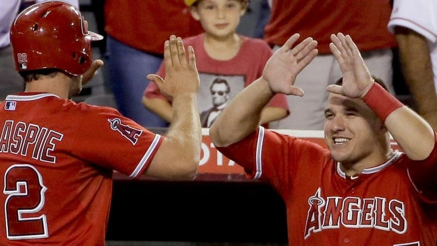 <p>Los Angeles Angels' Conor Gillaspie, left, celebrates after a two run home run in the dugout with Mike Trout during the sixth inning of a baseball game against the Cleveland Indians in Anaheim, Calif., Monday, Aug. 3, 2015.</p>