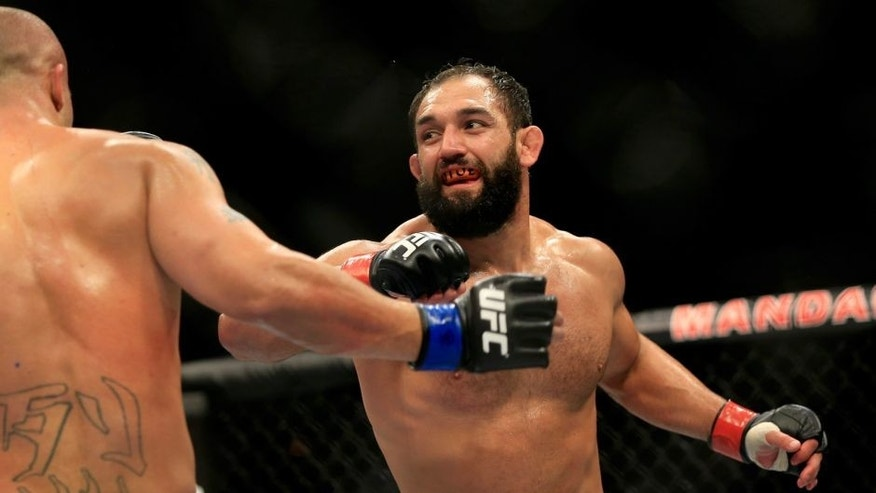 LAS VEGAS, NV - DECEMBER 06: Johny Hendricks punches Robbie Lawler in their welterweight title fight during the UFC 181 event at the Mandalay Bay Events Center on December 6, 2014 in Las Vegas, Nevada. (Photo by Alex Trautwig/Getty Images)