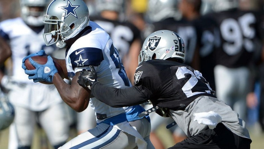 Aug 12, 2014; Oxnard, CA, USA; Dallas Cowboys receiver Dez Bryant (88) is defended by Oakland Raiders cornerback Tarell Brown (23) at scrimmage against the Oakland Raiders at River Ridge Fields. Mandatory Credit: Kirby Lee-USA TODAY Sports