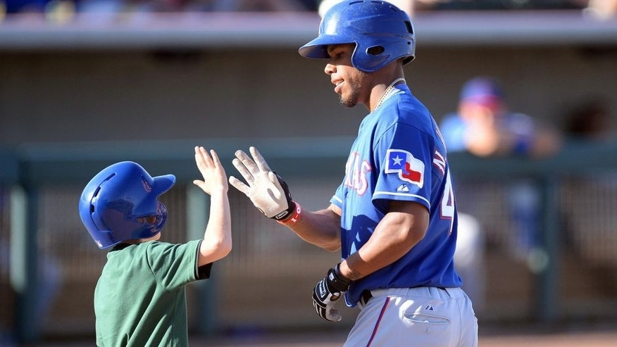 <p>Mar 15, 2014; Phoenix, AZ, USA; Texas Rangers outfielder Nick Williams slaps hands with a bat boy after hitting a home run in the ninth inningagainst the Oakland Athletics at Phoenix Municipal Stadium. The Rangers won 16-15. Mandatory Credit: Joe Camporeale-USA TODAY Sports</p>