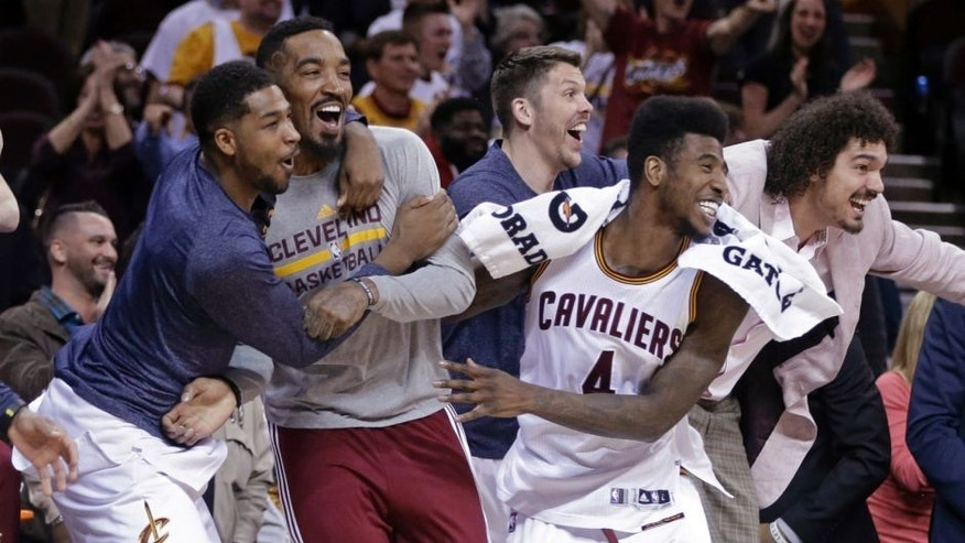 Cleveland Cavaliers' Tristan Thompson, left, J.R. Smith, second form left, Mike Miller, third from left, Iman Shumpert (4) and Anderson Varejao, right, celebrate after a 113-108 win in overtime over the Washington Wizards in an NBA basketball game Wednesday, April 15, 2015, in Cleveland. (AP Photo/Mark Duncan)