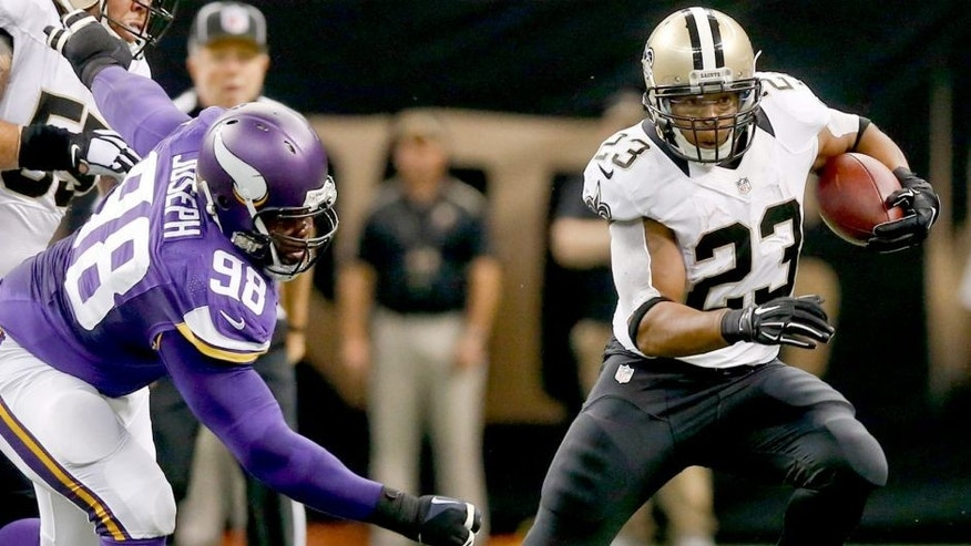 Sep 21, 2014; New Orleans, LA, USA; New Orleans Saints running back Pierre Thomas (23) runs from Minnesota Vikings defensive tackle Linval Joseph (98) during the first quarter of a game at Mercedes-Benz Superdome. Mandatory Credit: Derick E. Hingle-USA TODAY Sports