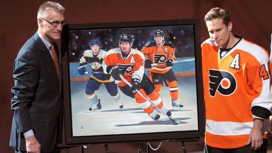 Mar 25, 2013; Philadelphia, PA, USA; Philadelphia Flyers General Manager Paul holmgren unveils a painting honoring Philadelphia Flyers defenseman Kimmo Timonen (44) for playing in his 1000th NHL game in his career at the Wells Fargo Center. Mandatory Credit: Eric Hartline-USA TODAY Sports