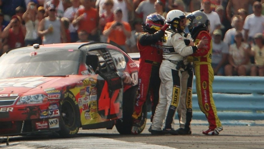 WATKINS GLEN, NY - AUGUST 12: Kevin Harvick, driver of the #29 Shell/Pennzoil Chevrolet, and Juan Pablo Montoya, driver of the #42 Wrigley's Big Red Dodge, are separated by NASCAR officials after the two collided during the NASCAR Nextel Cup Series Centurion Boats at The Glen at Watkins Glen International on August 12, 2007 in Watkins Glen, New York. (Photo by Chris McGrath/Getty Images) *** Local Caption *** Juan Pablo Montoya;Kevin Harvick