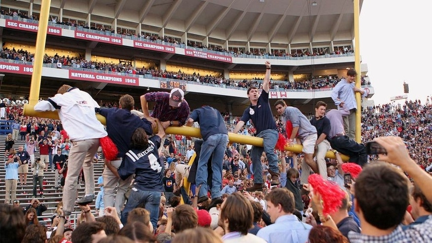 OXFORD, MS - OCTOBER 4: Fans of the Ole Miss Rebels hang on the goalpost while celebrating the victory over the Alabama Crimson Tide on OCTOBER 4, 2014 at Vaught-Hemingway Stadium in Oxford, Mississippi. Mississippi beat Alabama 23-17. (Photo by Joe Murphy/Getty Images)