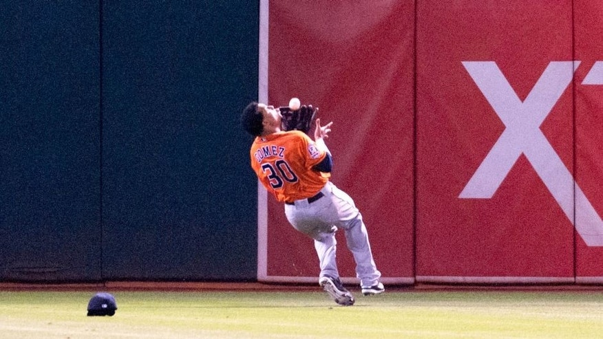 Aug 6, 2015; Oakland, CA, USA; Houston Astros center fielder Carlos Gomez (30) makes an over the shoulder catch against the Oakland Athletics during the fifth inning at O.co Coliseum. Mandatory Credit: Ed Szczepanski-USA TODAY Sports